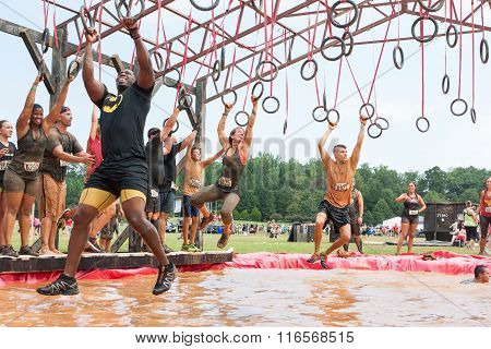 Competitors Swing From Rings Over Water At Extreme Obstacle Course