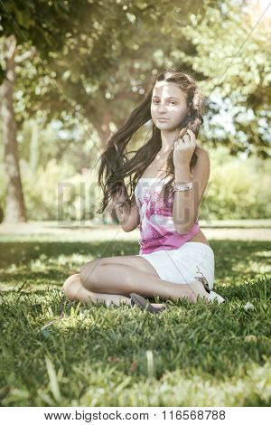 Girl With Long Hair Sitting In The Green Grass