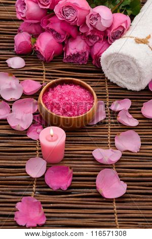 Pink rose with candle and petals,salt in bowl on mat