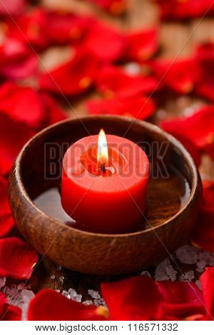Roses petals with pile of salt and candle in bowl on old wooden board