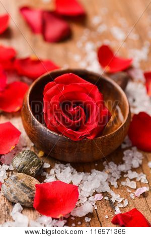 Roses petals with pile of salt ,stones and candle in bowl on old wooden board
