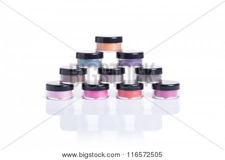 Bright natural eye shadows in transparent jars, isolated on white background