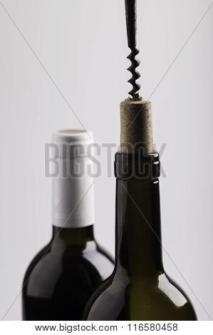 two wine bottles, cork and corkscrew on white background