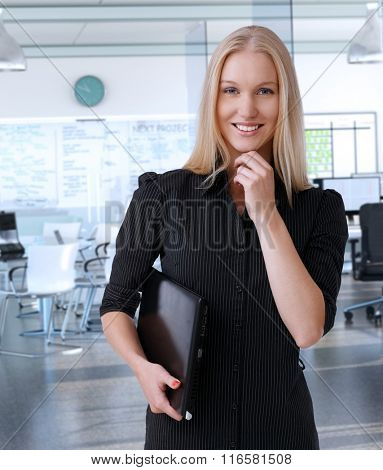 Young scandinavian businesswoman at corporate office, smiling.