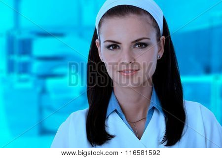 Close-up portrait of young caucasian female nurse in blue lit medical scanner room.