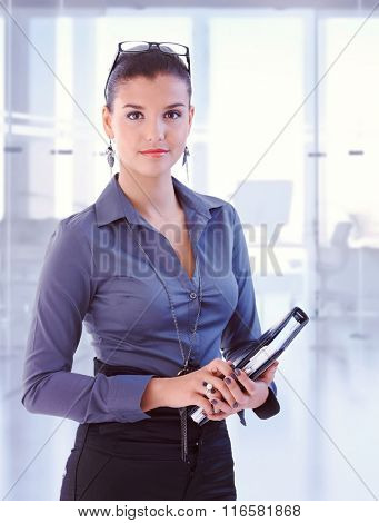 Young attractive brunette caucasian secretary standing at business office with personal organizer, looking at camera, smiling. Woman suit, copyspace.