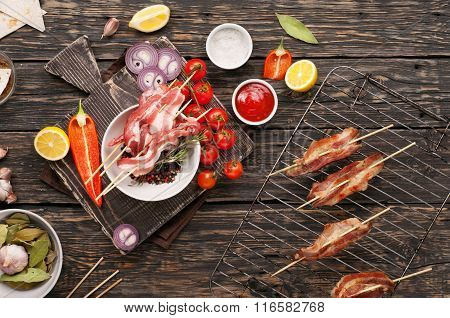 Raw Bacon Slices With Ready Grilled Bacon And Vegetables
