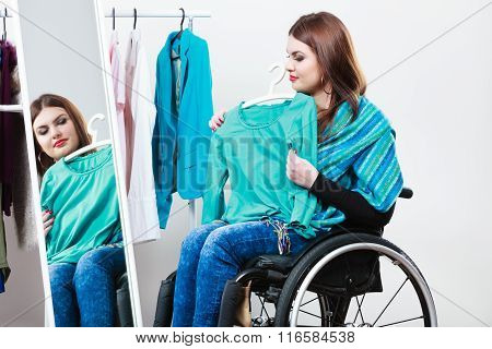 Invalid Girl On Wheelchair Choosing Clothes In Wardrobe
