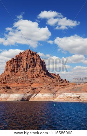 Scenic huge artificial pond Powell on the Colorado River, USA. The lake is surrounded by picturesque banks of red sandstone. Walk around the lake Powell at sunset