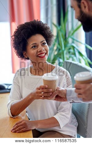 happy woman taking coffee from man in office