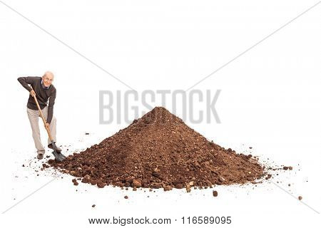 Cheerful senior shoveling a big pile of dirt and looking at the camera isolated on white background