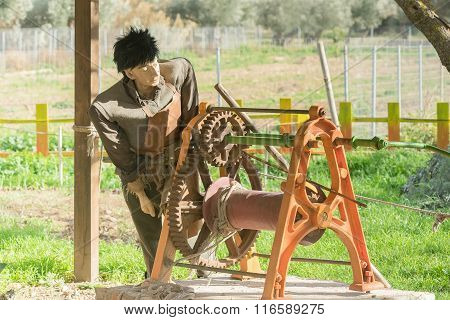 Model of an old traditional farm worker at a park.