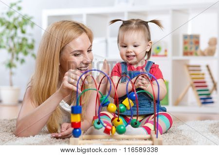 happy kid girl and mom playing toy