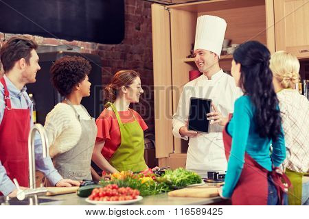 happy friends with chef and tablet pc in kitchen