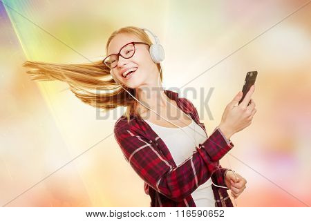 Teenager dancing to the music comming from her smartphone with headphones