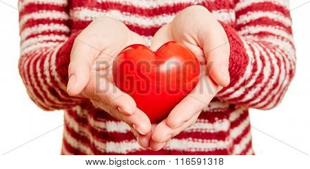 Hands holding a red hart as symbol for love and care
