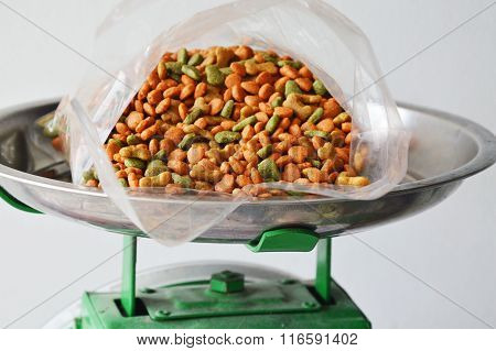 pet food in plastic bag on stainless weighing scale tray