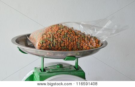 dog food in plastic bag on stainless weighing scale tray