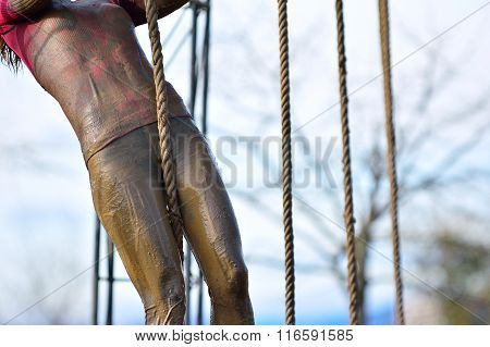 Woman In Dirty Sportswear Climb The Rope
