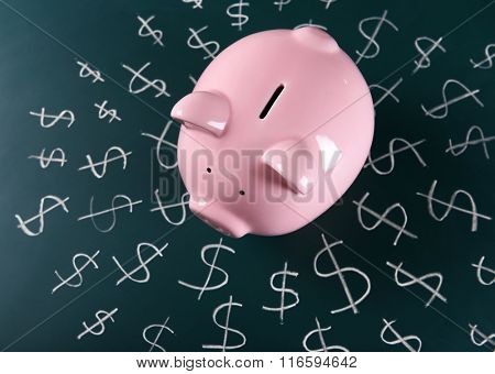 Piggy bank on a chalkboard with Dollar currency symbols