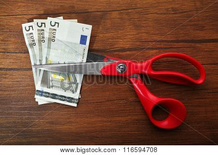 Red scissors cut money on wooden background. Financial concept