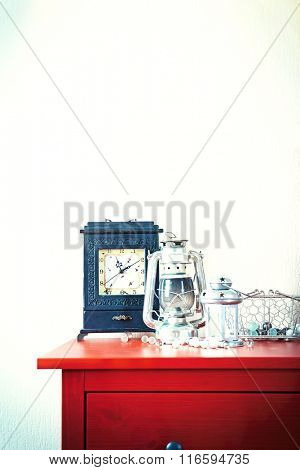 Room interior with red wooden commode, lanterns and clock on light wall background