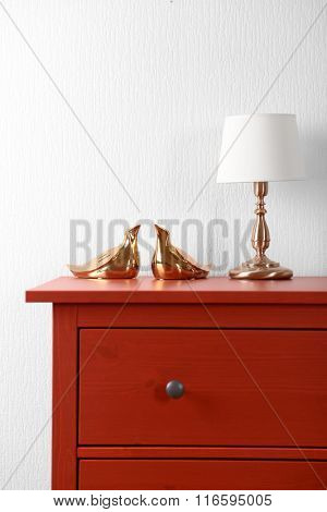 Room interior with red wooden commode and lamp on light wall background