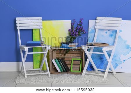 Room design with white chairs, bookcase, pictures, flowers over blue wall