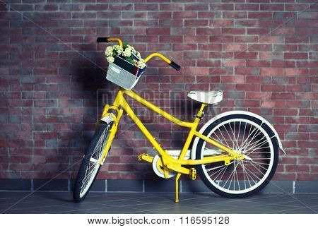 Yellow bicycle with books on brick wall background
