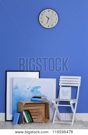 Room design with white chair, bookcase, pictures and clock over blue wall