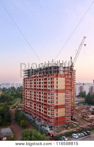 Stationary Hoist And Brick Tall Building Under Construction At Evening