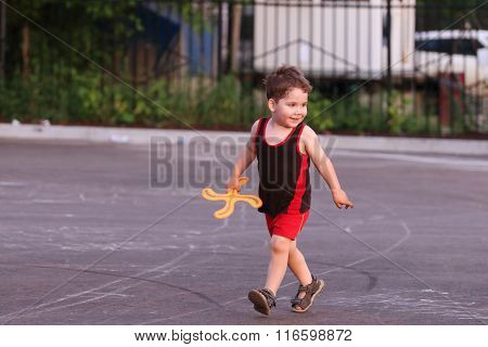 Happy Little Handsome Boy With Boomerang Runs In Summer Evening