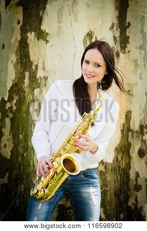 Woman with saxophone in nature