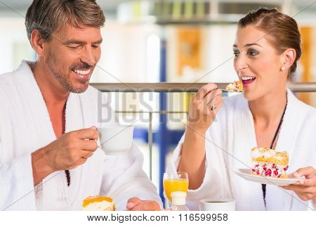 Woman and man eating snack with coffee and cake in thermal spa