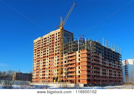 Tall Crane And Building Under Construction On Blue Sky At Sunny Winter Day