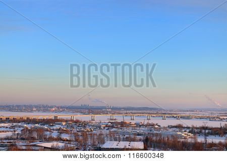 Bridge Over Frozen River And Panoramic View Of City In Cold Winter Evening