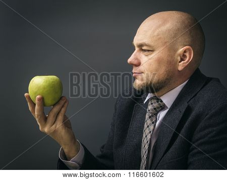 Portrait of an adult man in a business suit on a black background.Healthy  man nutritionist  holding an apple as a healthy alternative