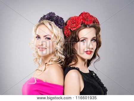 Portrait of two gorgeous, smiling women wearing flower alike bijouterie over grey background.