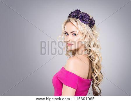 Side view of beautiful blond wearing a purple flower alike headband over grey background.