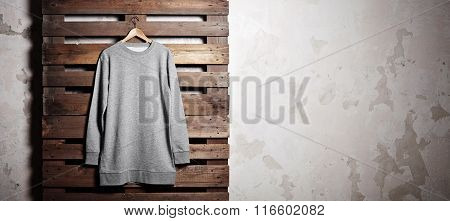 Photo grey hoody  hanging in front of wood background