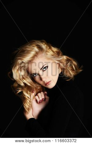 Portrait of a beautiful blonde woman with stunning eyes over black background.  Beauty, fashion. Make-up, smoky eyes.