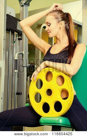 Slender young woman is training with weights at the gym. Active lifestyle, bodycare. Fitness equipment.