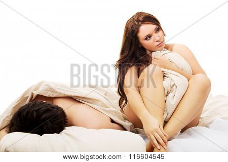 Woman sitting on the bed wrapped with quilt.