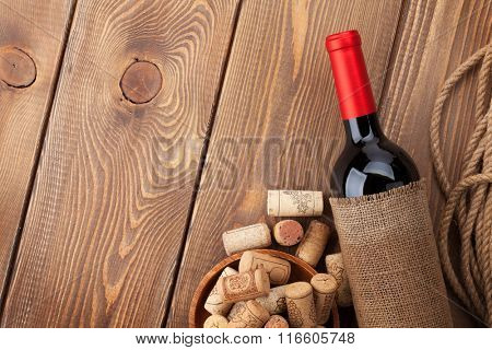 Red wine bottle and corks over wooden table background. Top view with copy space