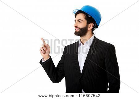 Engineer in protective helmet pointing up.