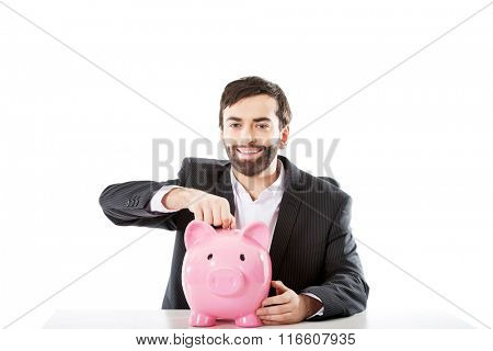 Businessman putting a coin to piggybank.