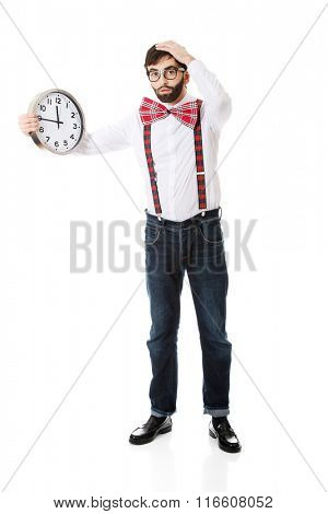 Man wearing suspenders holding big clock.