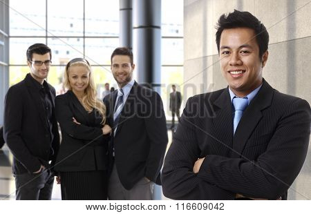 Successful asian businessman leading business team, happy people at office lobby.