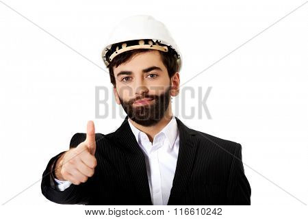 Engineer in protective helmet with thumbs up.
