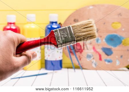 Large paintbrush on a white and yellow background. Palette with tempera paints